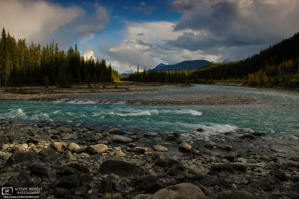 The last beams of sunlight are hitting rocks along the Athabasca River in Jasper National Park, Alberta, Canada.