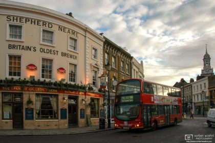 A double-decker bus is passing the Spanish Galleon Tavern, a historic 19th century pub near Cutty Sark in Greenwich, London.