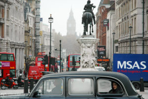 A taxi passenger taking in a view of the surroundings on Trafalgar Square, London, England.