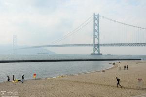 Beachside activities against the backdrop of Akashi Kaikyō, the beautiful suspension bridge in Kobe, Japan.