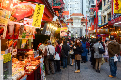 A foodie pictured amidst a variety of food choices in the Chinatown of Kobe, Japan.