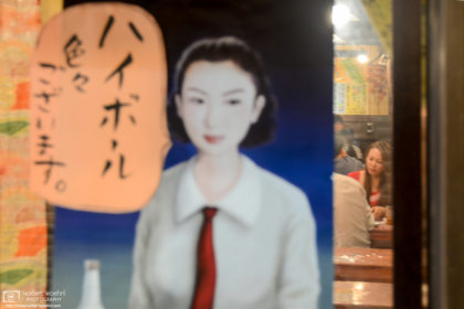 View into an Izakaya (Japanese-style pub) through a Showa-period highball advertisement as seen in Kyoto, Japan.