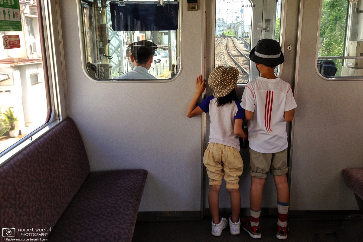 Kids enjoying the driver's perspective while riding a Kintetsu Line train in Kyoto, Japan.