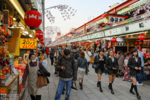 High school girls walking along Nakamise-dori, the shop-lined approach to Sensoji Temple in Asakusa, Tokyo, Japan.
