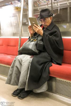 Priest using Tablet Computer on Subway Train, Shinjuku, Tokyo, Japan Photo