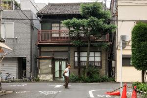 An old woman walking through a residential neighborhood in Taito-ku, Tokyo, Japan.