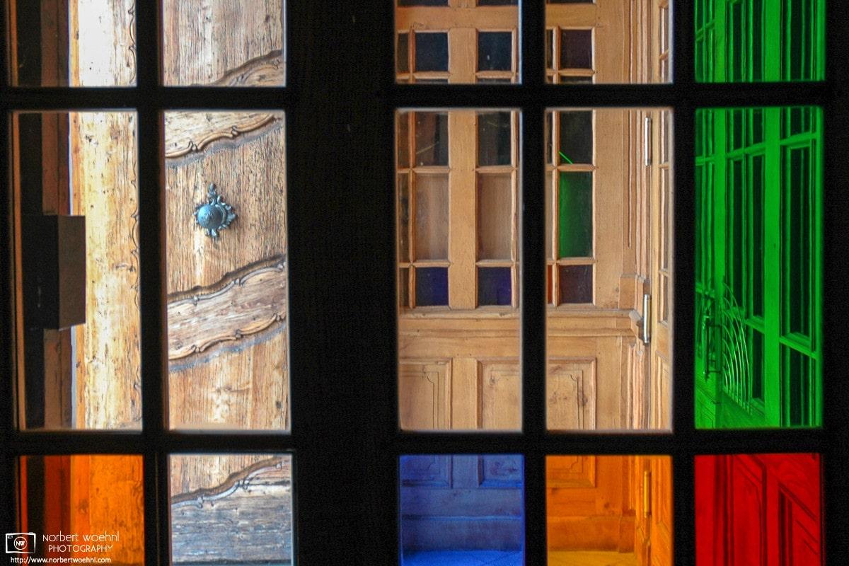 A pattern of colorful glass windows around the main entrance of Mariatrost Basilica in Graz, Austria.