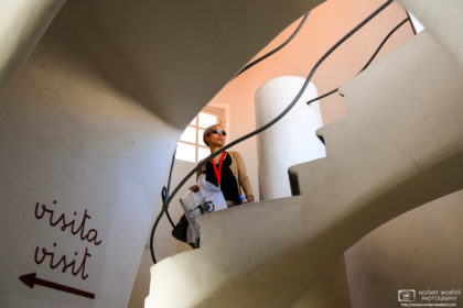 A visitor walking a spiral staircase inside Casa Batlló, Antoni Gaudí's architectural masterpiece in Barcelona, Spain.