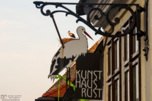 "A white stork is seen in its rooftop nest in the ""stork village"" of Rust, Austria, behind a locally-themed sign on a building."