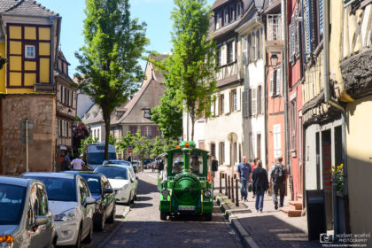 "A colorful ""tourist train"" vehicle is seen navigating the old cobblestone streets of Colmar in Alsace, France."