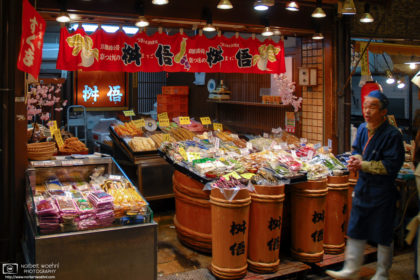 At Nishiki Market in Kyoto, Japan, a shop owner is seen outside his shop selling a variety of pickled vegetables.