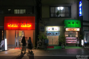 Evening view of a grill restaurant and a sushi shop in the Nakajuku district of Itabashi-ku, Tokyo, Japan.