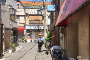 The postman is coming to this old corner in the Takinogawa area of Kita-ku in Tokyo, Japan.