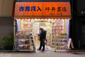 A customer is weighing a purchase at a small neighborhood bookstore in Itabashi-ku, Tokyo, Japan.