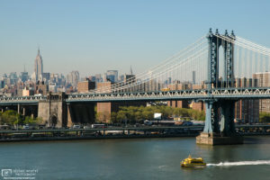 A water taxi is seen on the East River with Williamsburg Bridge and lower midtown in the background; New York City, USA.