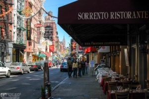 A street in Little Italy with the Empire State Building visible in the distance; New York City, USA.
