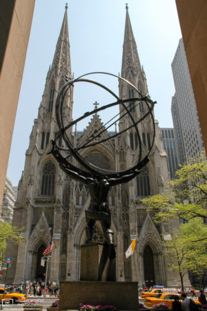 St. Patrick's cathedral is seen behind the Atlas Statue at Rockefeller Center in New York City, USA.