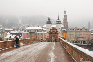 Walking the dog on a cold winter day at Alte Brücke (Old Bridge) in Heidelberg, Germany.