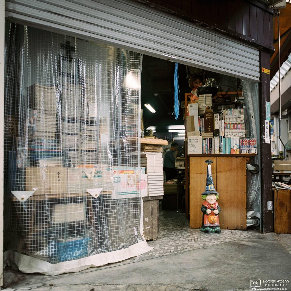 A friendly figure is seen standing beside a bookshelf at an antiques shop inside Gondo shopping street, Nagano, Japan.