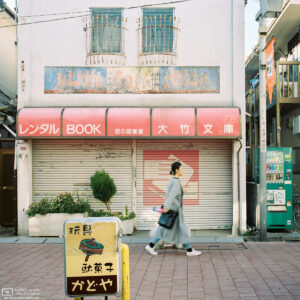 A woman walks past the slightly dated facade of a rental book store in Koenji, Tokyo, Japan.