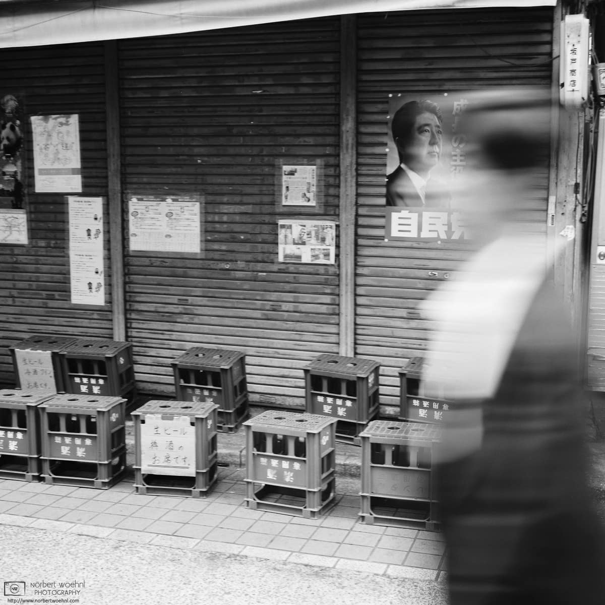 At Yanaka Ginza in Tokyo, Japan, a woman is walking past a shop that is decorated with a poster of Shinzo Abe.