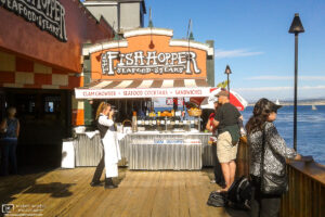 Staff are snapping a photo of a family outside an oceanside restaurant in Monterey, California.