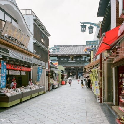 Approaching Kawasaki Daishi (Heiken-ji) Temple in Kawasaki, Japan, along a road lined with shops.