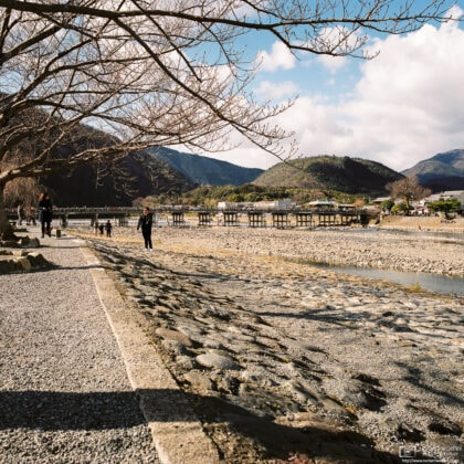 A view along Katsura River in Arashiyama, Kyoto, Japan. Togetsukyo Bridge is visible in the background.
