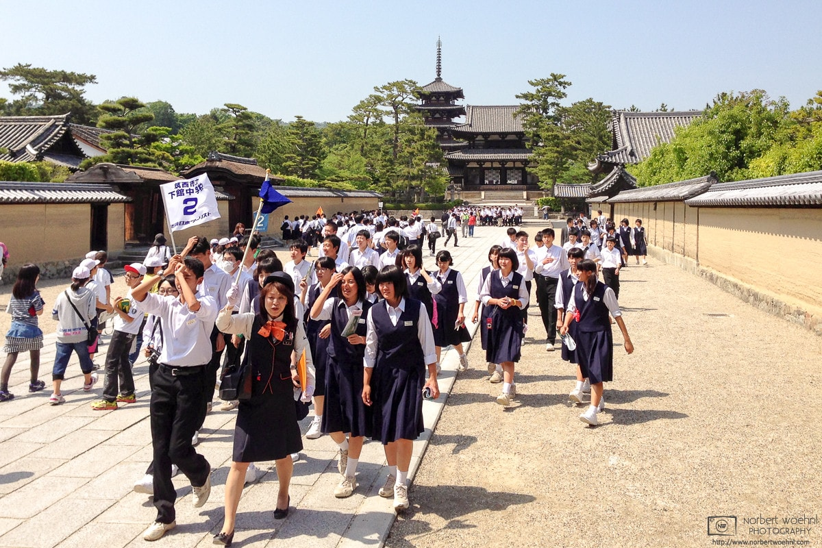 Students are taking a guided tour outside Hōryūji Temple (法隆寺) in Nara, Japan.