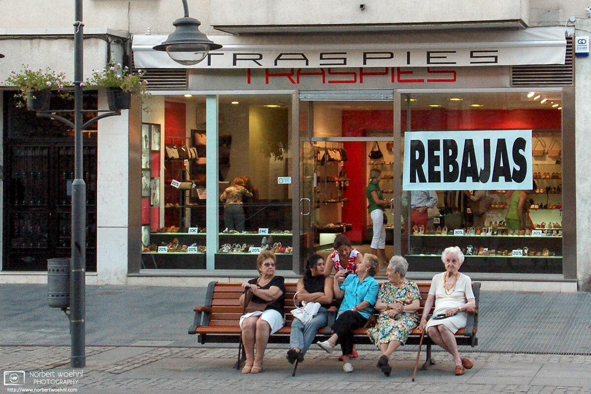 Ladies enjoying a summer afternoon chat in a quiet residential and shopping area of Madrid, Spain.