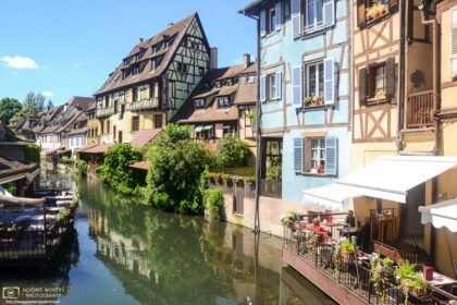 Restaurants and half-timbered buildings along the Lauch River in the historic center of Colmar, France.