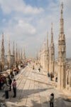 Tourists taking in the incredible views from the rooftop of Duomo di Milano, the cathedral church of Milan, Italy.