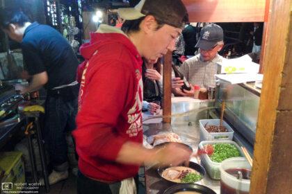 Staff preparing servings of Ramen noodles inside a typical Yatai food stall in Fukuoka, Japan.
