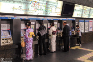 At Kyoto Station in Japan, kimono-clad women are buying train tickets at ticket machines.