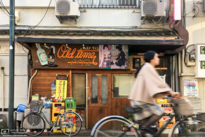 A bicyclist is passing in front of an old restaurant in the Kita Ward of Tokyo, Japan.