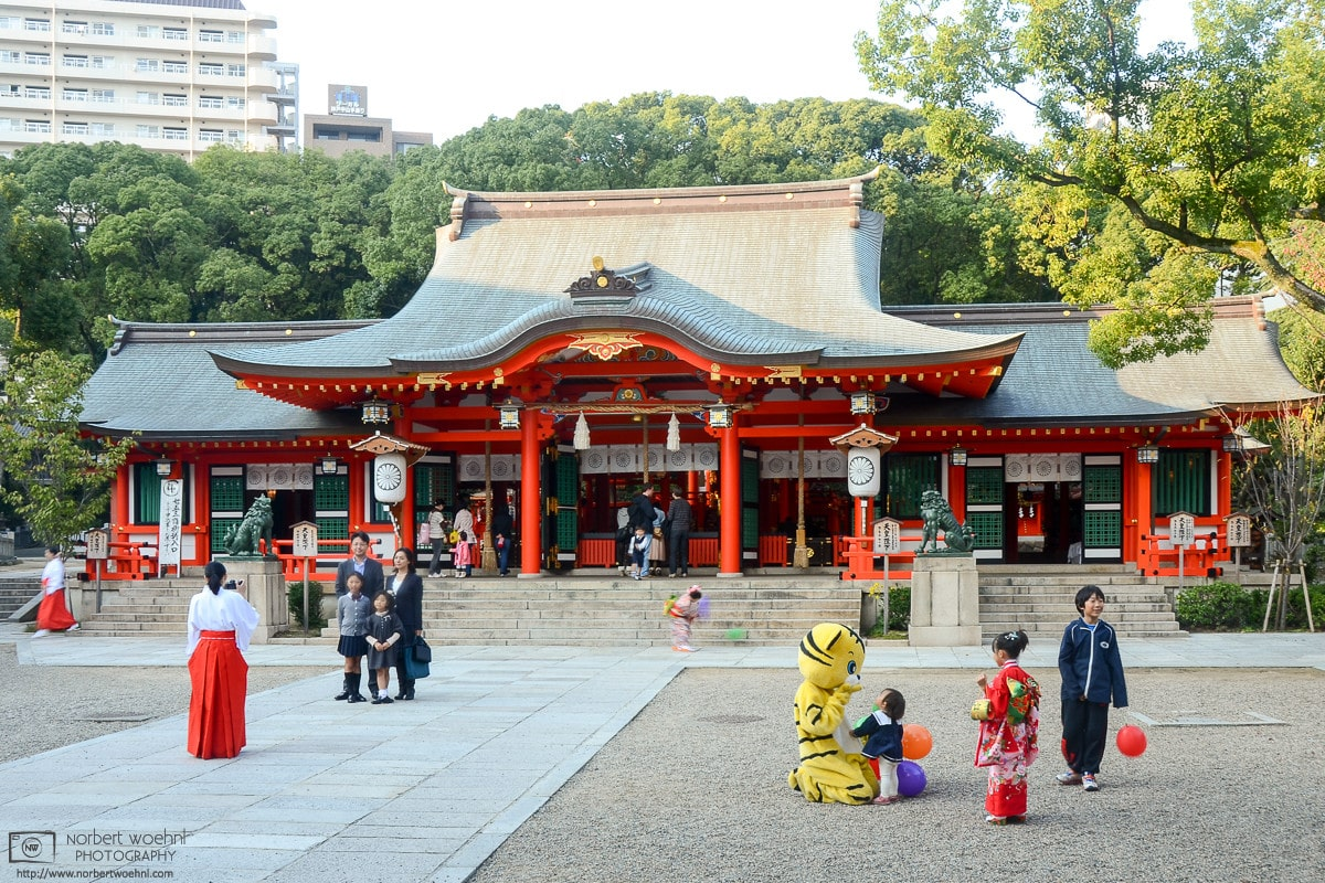 Visitors and shrine maiden are engaging in various activities outside the main hall of Ikuta Shrine in Kobe, Japan.