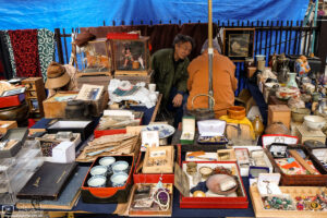 Flea market vendors are having a chat amidst their colorful merchandise at Toji Temple in Kyoto, Japan.