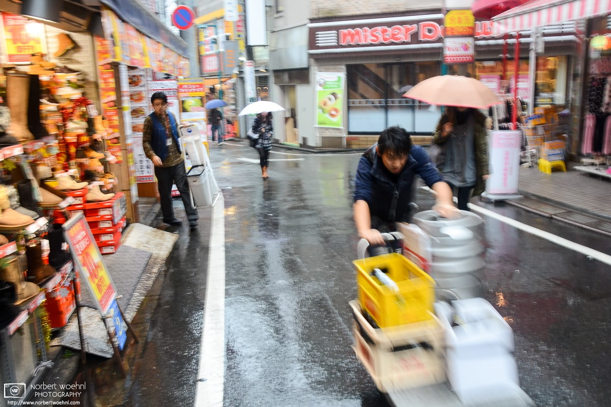 During pouring rain, a delivery person is pushing a cart with beverage containers around Shimokitazawa in Tokyo, Japan.