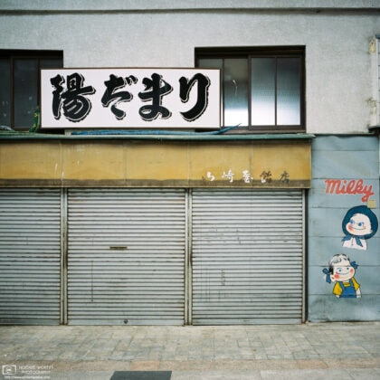 At Gondo Shopping Street in Nagano, an advertisement mural is painted on the wall beside an old shop.