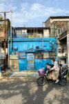 A fully occupied bicycle passes a colorful building in the Kirigaoka area of the Kita ward in Tokyo, Japan.