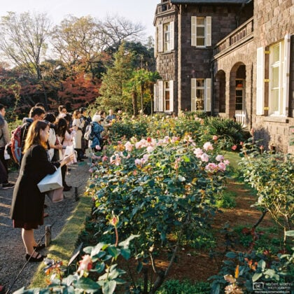 Visitors are watching flowers outside a western-style mansion building at Kyū-Furukawa Gardens in Tokyo, Japan.