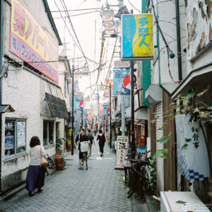 Pedestrian and bicycle traffic along Star Road, a pub-lined alley in Asagaya, Tokyo, Japan.