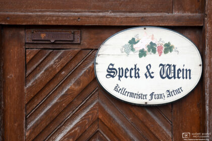 """A sign advertising the sale of bacon and wine (""""Speck & Wein"""") in the village of Sankt Margarethen in eastern Austria."""