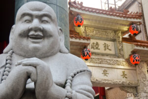 A statue of a laughing Buddha greets visitors at the entrance to the Chinatown of Kobe, Japan.